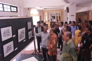 Abd. Aziz Ahmad sedang menjelaskan makna sebuah karya kaligarafi kepada Prof. Dr. Haryono Suyono serta pengunjung lainnya.